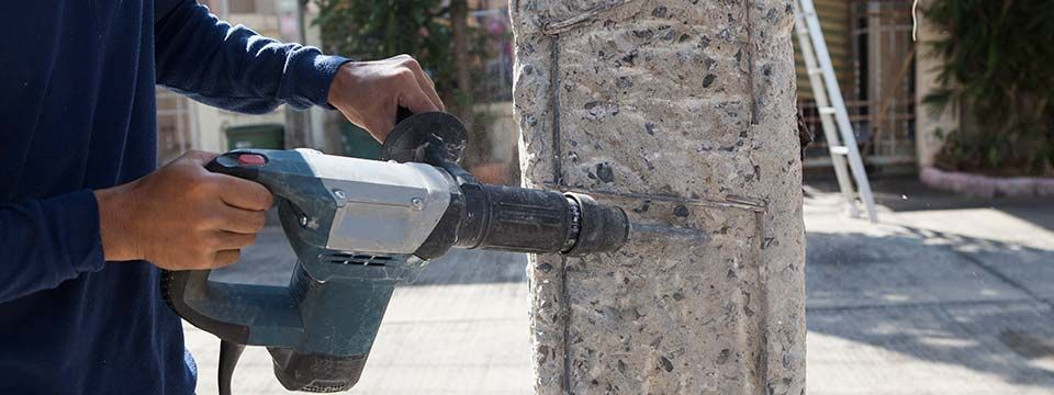 worker hand drilling on concrete pole for construction building
