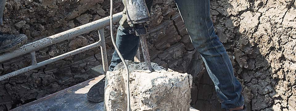 man drilling cement concrete stake